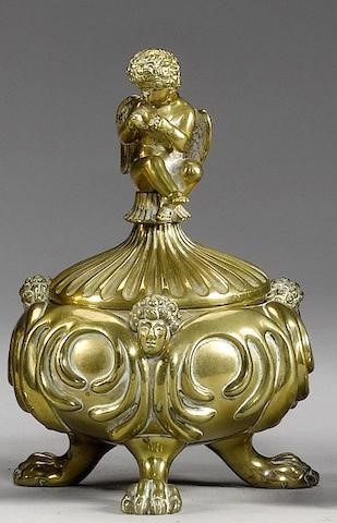 Image of Petrach's inkstand.-  the lid decorate with a seated Cupid, inscribed to the underside 'PETRARCH'S INKSTAND' and with a ten-line poem beneath, 'By beauty won from soft Italia's land', enclosing a gilt brass inkwell, the compressed spherical body applied with masks, on three paw supports, 17 cm highGold