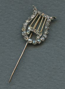 Image of a gold tie pin in the form of a four-stringed classical lyre, decorated with diamonds set in silver