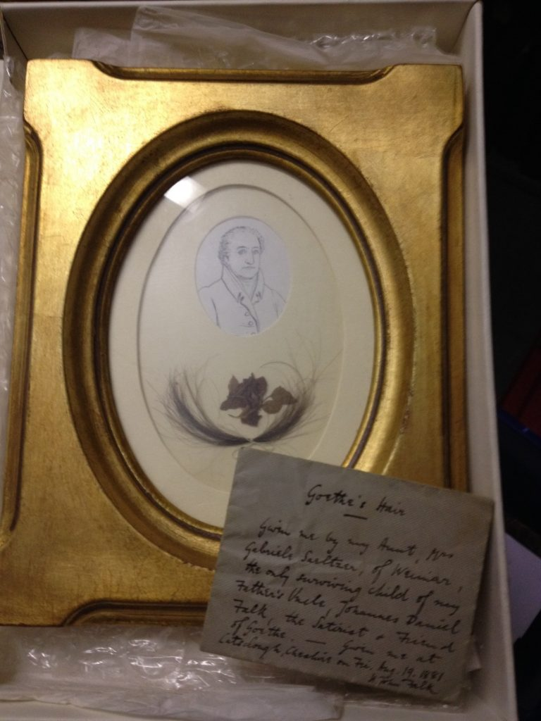 A lock of hair framed with a portrait in an oval, gold frame.
