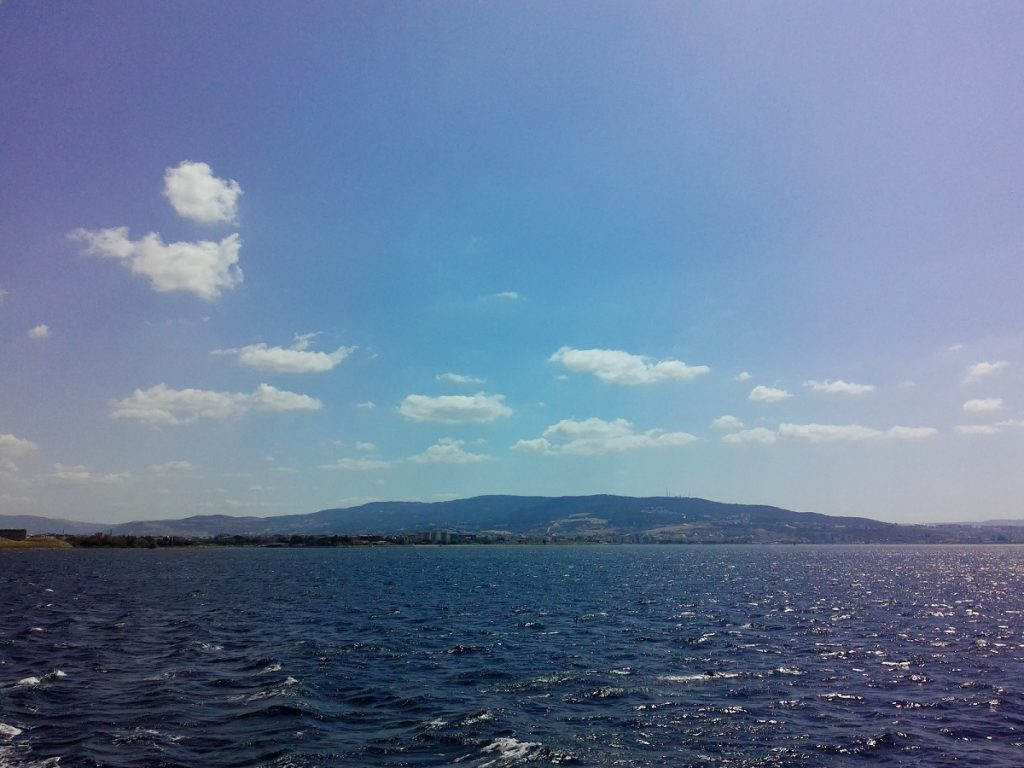 Image of The Hellespont. A hilly horizon with blue water below and blue sky above