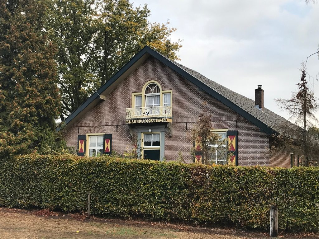 Image of a farmhouse with a high hedge in front of it.