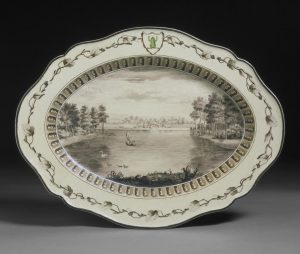 Oval, cream coloured earthenware plate from the 'Frog Service', painted with a view of the lake at West Wycombe, Buckinghamshire.