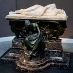 Image of a white marble statue of Percy Shelley's drowned body on a plinth.